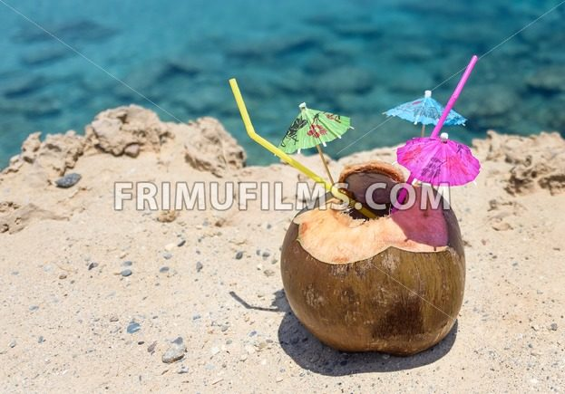 Coconut with drinking straw, umbrellas and flowers, on sand at the sea in protaras, cyprus island - frimufilms.com