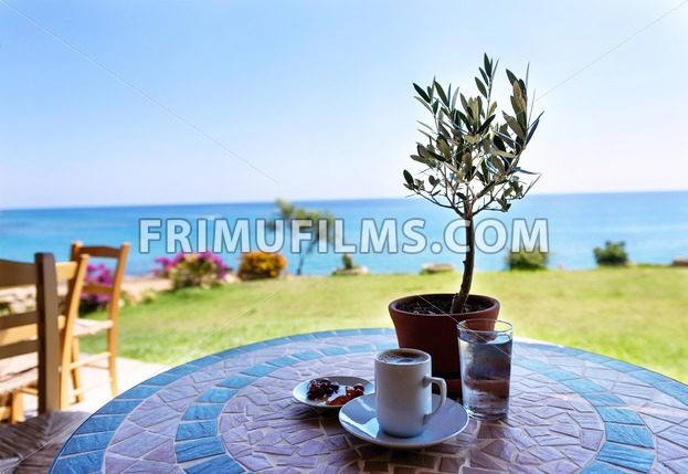 Cup of coffee on a table with olive tree - My Blog
