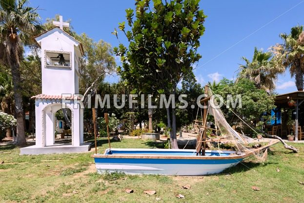 Photo of a white bell tower and a sailor boat on a beach in protaras - frimufilms.com