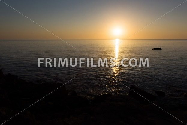 Sunrise with reflection of light in the water, in protaras paralimni, a fishing boat - frimufilms.com
