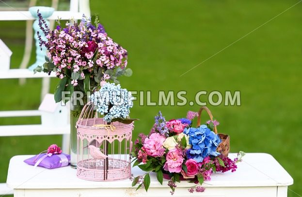 Vintage wedding decoration with white table, flowers and parrot cage - frimufilms.com