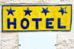 Big blue yellow hotel sign on wall with white copyspace plate, 4 stars