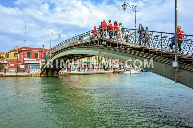 VENICE, ITALY – APRIL 02, 2017: Daylight view to Venetian Lagoon canal with parked boats and tourists walking on sidewalk and bridge. Bright blue sky and historic architecture buildings. Murano Island - frimufilms.com