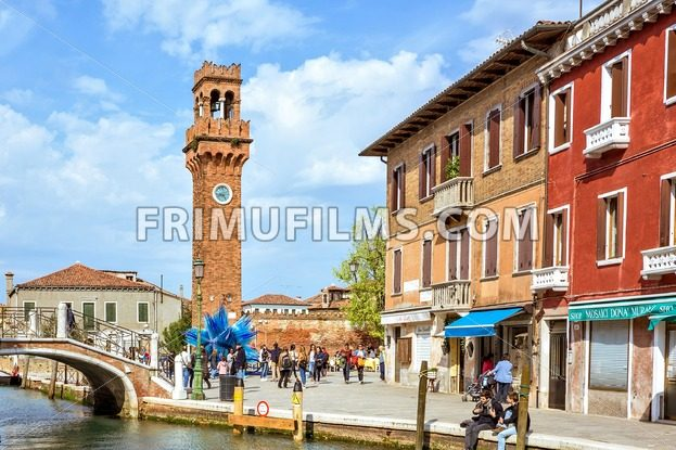 VENICE, ITALY – APRIL 02, 2017: Daylight view to colorful Blue Murano Glass Sculpture with tourists walking and clock tower. Bright blue sky with clouds. Murano Island, Venice, Italy - frimufilms.com
