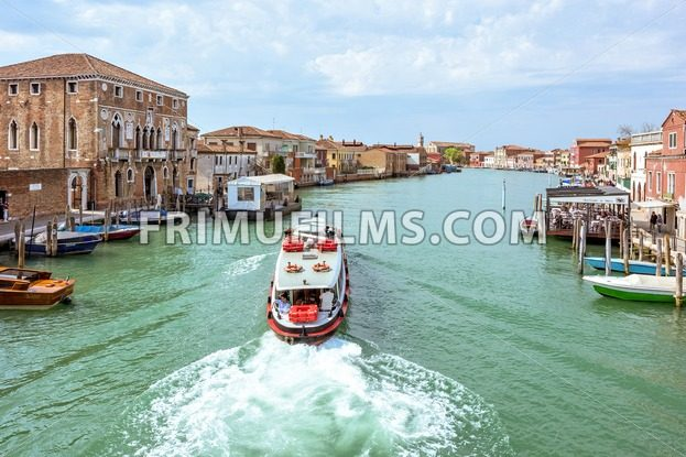 VENICE, ITALY – APRIL 02, 2017: Daylight view to transportation ship cruising to station in Venice Lagoon canal. Parked boats and people walking on sidewalk. Bright blue sky with clouds. Murano Island - frimufilms.com