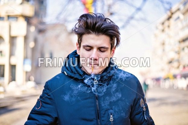 Young handsome caucasian boy with long stylish haircut smoking a black cigar in the street, looking down, inhale smoke. Dark blue coat - frimufilms.com